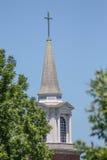 Kirchen-Kirchturm gegen blauen Himmel mit grünen Bäumen Lizenzfreie Stockbilder