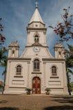 Kirchenfassade und Glockenturm vor einem kleinen Kopfstein quadrieren mit immergrünem Garten, an einem sonnigen Tag bei São Manu stockfotografie