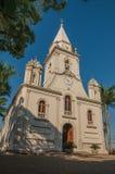 Kirchenfassade und Glockenturm vor einem kleinen Kopfstein quadrieren mit immergrünem Garten, an einem sonnigen Tag bei São Manu stockbild