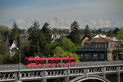 Kirchenfeldbrucke Bridge over Aare river in Bern. Switzerland. Kirchenfeldbrucke Bridge over Aare river with local legendary red tram and Swiss Alps in Royalty Free Stock Images