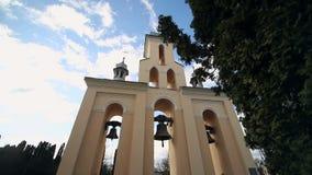 Kirchenglocken an einem sonnigen Tag in einem starken Wind Der Wind rüttelt die Bäume nahe dem Glockenturm und Sonechka-Glanz in stock video footage
