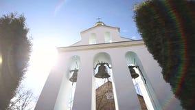 Kirchenglocken an einem sonnigen Tag in einem starken Wind Der Wind rüttelt die Bäume nahe dem Glockenturm und Sonechka-Glanz in stock video