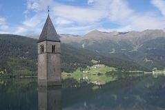 Kirchenglocketurm im See Resia stockbilder