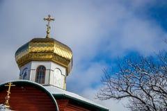 Kirchenhaube und schneebedeckte Winterbaumaste gegen den blauen Himmel Lizenzfreie Stockbilder