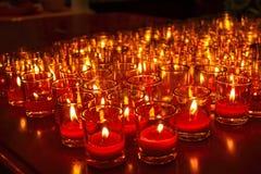 Kirchenkerzen in den roten transparenten Leuchtern Stockfotos
