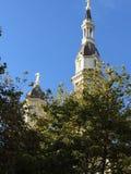 Kirchenkirchtürme hinter Bäumen Stockbild