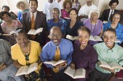 Kirchenversammlung, die auf Kirchenbänken mit hoher Winkelsicht des Bibelporträts sitzt Lizenzfreies Stockfoto