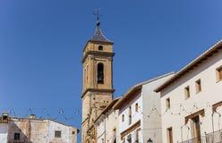 Kirchturm und weiße Häuser am zentralen Platz von Requena Stockbild