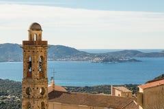 Kirchturm von Lumio mit Calvi im Hintergrund Stockbild