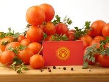 Kirgisistan-Flagge auf einer Holzverkleidung mit den Tomaten lokalisiert auf einem wh Lizenzfreie Stockbilder