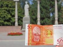Kirgizisk sedel med Kurmanjan Datka på bakgrunden av hennes monument i Bishkek Royaltyfria Bilder