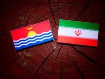 Kiribati flag with Iranian flag on a tree stump isolated Royalty Free Stock Photos