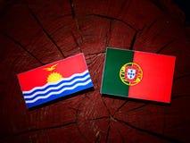 Kiribati flag with Portuguese flag on a tree stump isolated. Kiribati flag with Portuguese flag on a tree stump royalty free illustration