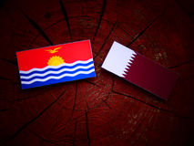 Kiribati flag with Qatari flag on a tree stump isolated. Kiribati flag with Qatari flag on a tree stump Royalty Free Stock Images