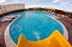 Kirillovka, Ucrânia - 28 de agosto de 2016: Corrediça de água amarela e uma grande piscina Imagens de Stock Royalty Free