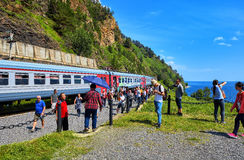 KIRKIREY, het GEBIED van IRKOETSK, RUSLAND - Juli, 29.2016: Toeristen van verschillende landen die gezichten van Spoorweg circum- stock foto