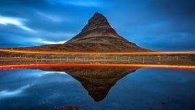 Kirkjufell berg och reflexion med billjus, Island royaltyfri foto