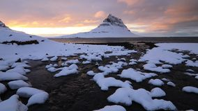 Kirkjufell mountain and river at winter sunrise, Iceland. stock video footage