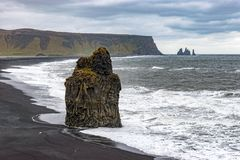 Kirkjufjara y Reynisfjara vara en Islandia con el cielo que amenaza Foto de archivo