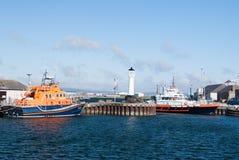 Kirkwal, het Verenigd Koninkrijk - Februari 19, 2010: overzeese haven met schepen en vuurtoren op blauwe hemel Watervervoer en Stock Afbeeldingen