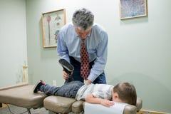 Kiropraktor som i regeringsställning justerar barnet royaltyfri bild
