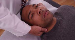 Kiropraktor som kontrollerar halsskada av den afrikanska manliga patienten royaltyfria bilder