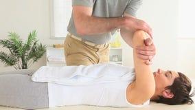 Kiropraktor som sträcker skuldran av en kvinna lager videofilmer