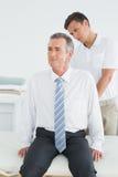 Kiropraktor som undersöker den mogna mannen royaltyfria bilder