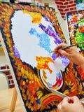 KIROV, RUSIA - 6 DE AGOSTO DE 2017: Mujer adulta que dibuja el ramo colorido en la lona en el estudio local del arte Foto de archivo libre de regalías