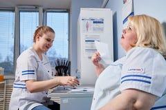 Kirov, Rusland - Februari 16, 2019: Ervaren artsen vette vrouw en strevende jonge arts sittins bij de lijst stock afbeelding