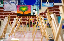 KIROV, RUSSIA - JUNE 23, 2017: Canvases standing in a row on the long table in the local art studio royalty free stock photo