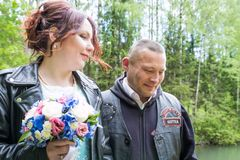 Unusual wedding couple including bride and groom in rocker leather jacket in the green park. Kirov, Russia - June 15, 2018: Unusual wedding couple including stock photos