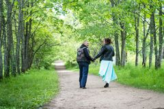 Unusual wedding couple including bride and groom in rocker leather jacket in the green park. Kirov, Russia - June 15, 2018: Unusual wedding couple including royalty free stock photo