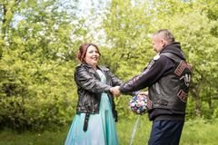 Unusual wedding couple including bride and groom in rocker leather jacket in the green park. Kirov, Russia - June 15, 2018: Unusual wedding couple including royalty free stock photos