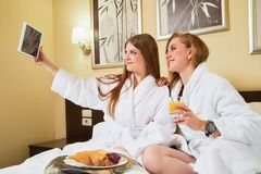 Free Kirov, Russia - March 02, 2019: Two Beautiful Girls In The Hotel Interior. Female Travelers Taking Selfies On A Tablet Stock Photo - 150862700