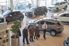 Manager, customer and cars in showroom of dealership Nissan in Nizhny Novgorodcity in 2018 royalty free stock photography