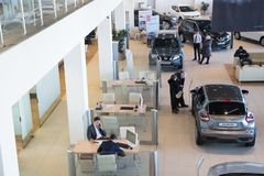 Manager, customer and cars in showroom of dealership Nissan in Nizhny Novgorodcity in 2018 royalty free stock images
