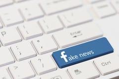 KIROVOGRAD UKRAINA, MARS, 12,2018 - tangenten med text fejkar nyheterna på det vita bärbar datortangentbordet Facebook stil Arkivfoton