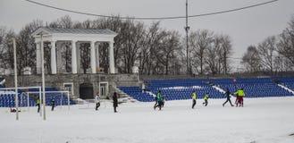 Kirovsk,俄罗斯,2019年3月17日 儿童游戏橄榄球在雪的体育场内 库存照片