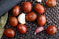 Kirsch-Tomaten Mini-Kumato, Knoblauch und Lorbeer lizenzfreie stockbilder