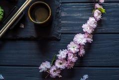 Kirschblüte und Geräte für Sushi auf einer schwarzen Tabelle stockfotografie