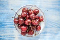 Kirsche auf Platte auf Purplehearthintergrund lizenzfreie stockfotos