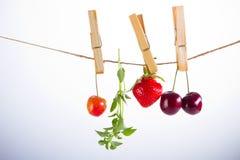 Kirsche, Erdbeere und Seil auf Weiß mit Rohrschelle lizenzfreie stockfotografie