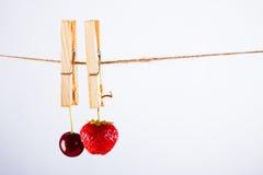 Kirsche, Erdbeere und Seil auf Weiß mit Rohrschelle lizenzfreie stockfotos