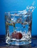 Kirsche spritzte in Wasser Stockfotos