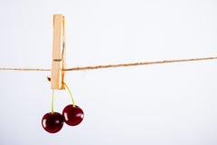 Kirsche und Seil auf Weiß mit Rohrschelle Stockfotografie