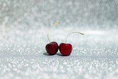 Kirsche zwei auf Funkelnhintergrund Stockfotos