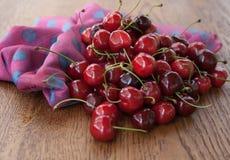 Kirschen auf Holztisch mit Wasser lässt Makrohintergrund fallen Stockfoto
