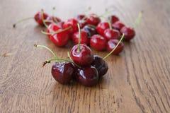 Kirschen auf Holztisch mit Wasser lässt Makrohintergrund fallen Stockfotos