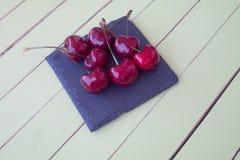 Kirschen auf Schiefer auf einer grünen Tabelle Stockbilder